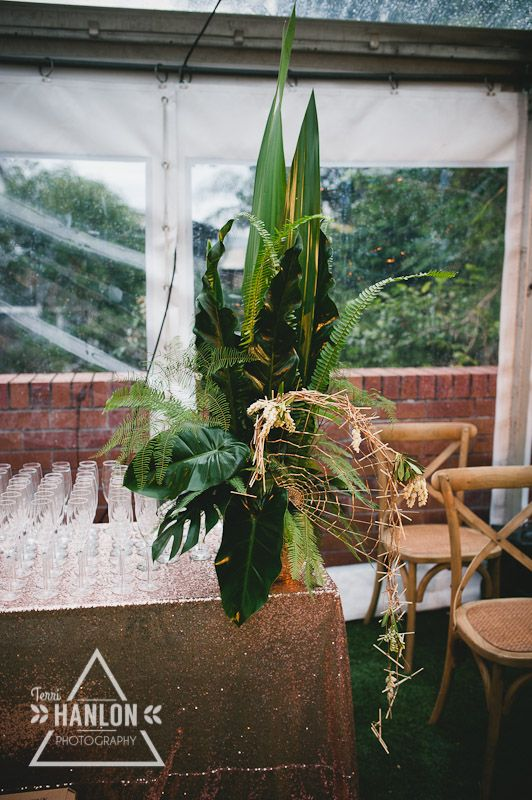 Tropical Foliage Arrangement - featuring a gold fan adorned with white Andromeda #tropical #WFML #francescasflowers