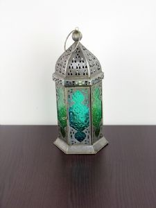 This large moroccan style hanging lantern is made from iron with two tones of patterned glass panes. Can be hung or placed on a table inside or outside. It holds a tea light candle which brings out beautifull shades in the coloured glass panes when alight. Available in Turquoise/Green, Orange/Yellow and Purple/Pink.