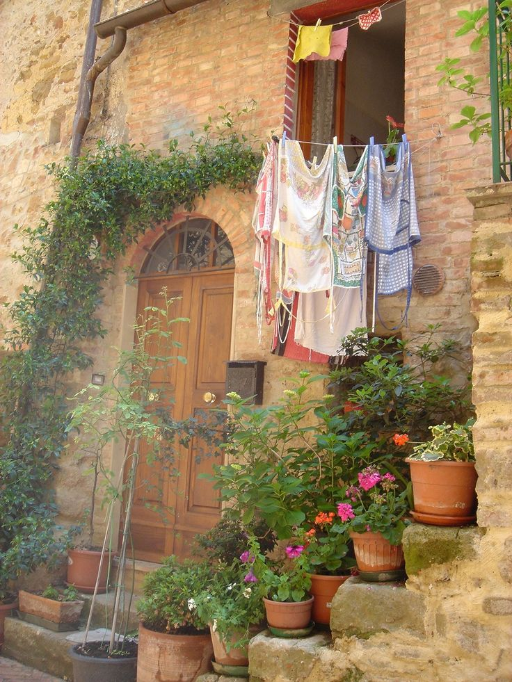A typical doorway in the lovely town of Pienza: flowers, laundry, ancient grey stone and brick.