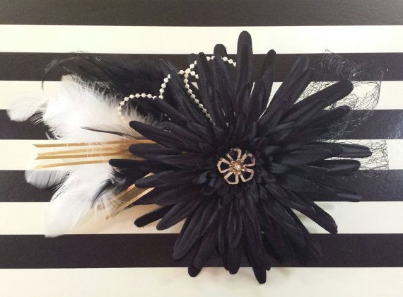 Gatsby inspired black fascinator with gold, white and pearl accents. An elegant and timeless hairpiece. Measures 9 by 6 and is mounted on a 3.5 by