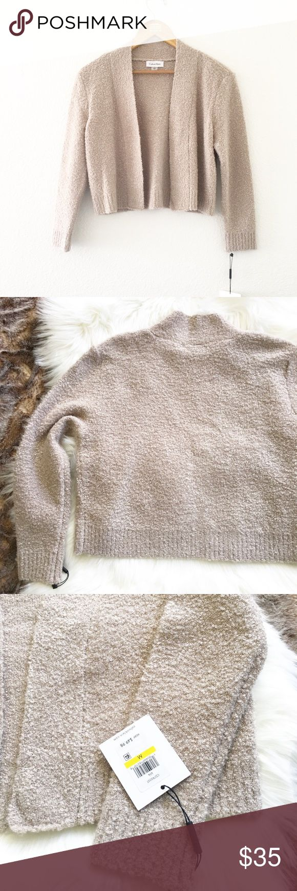 NWT Calvin Klein Tan Boucle Shrug Sweater NWT  Calvin Klein Brand Tan Boucle (soft ) Shrug Long Sleeve Sweater Slight stretch  Cropped design  Tan Color  Size Medium  18 inches Long  19 across with front closed Materials are-Acrylic + Nylon + Wool + 2% spandex Calvin Klein Sweaters Shrugs & Ponchos