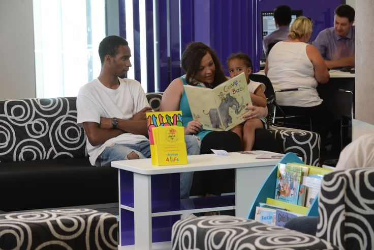 Young mum reads to her daughter while waiting her turn in the customer services centre.  Library staff maintain a small number of book displays on this floor for children and adults.