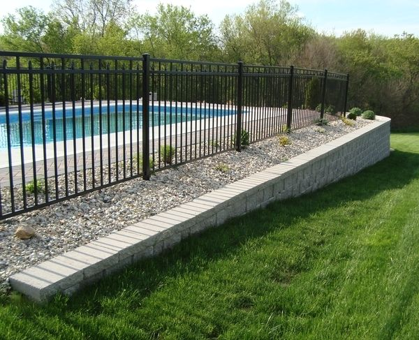 A retaining wall made of StoneWall Select block stabilizes the area around an in-ground pool.