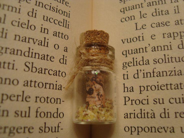 manca il gancio ma è un ciondolo per collana con una piccola mappa del tesoro e un po' di sabbia poi ho aggiunto una piccola perla sul cordoncino con un po' di colla a caldo