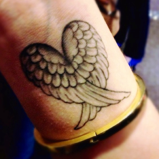 Closed wings heart tattoo