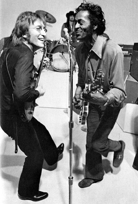 John Lennon and Chuck Berry, 1972, playing their guitars together at the microphone.