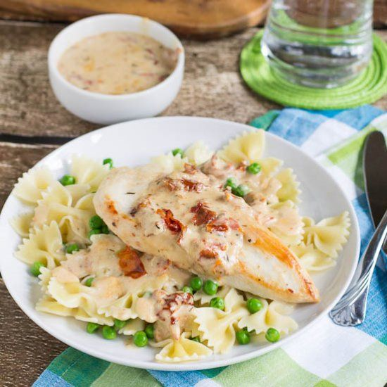Chicken with a creamy Sun-dried Tomato Sauce served over farfalle and peas. An easy weeknight meal!