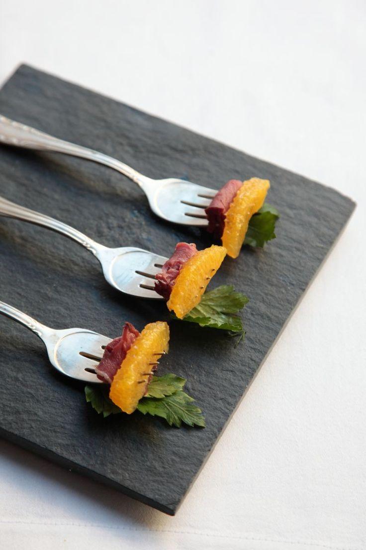 bereiden:Pel de sinaasappel tot op het vruchtvlees, verwijder zorgvuldig alle wit en snijd in partjes.Snijd de gerookte eendenborst in plakjes van ca. 1/2 cm dik.Verwijder de vette rand van de eendenborst.serveren:Neem een vork en prik de rolletjes vlees erop. Werk af met sinaasappel, peterselie en grof gemalen zwarte peper.