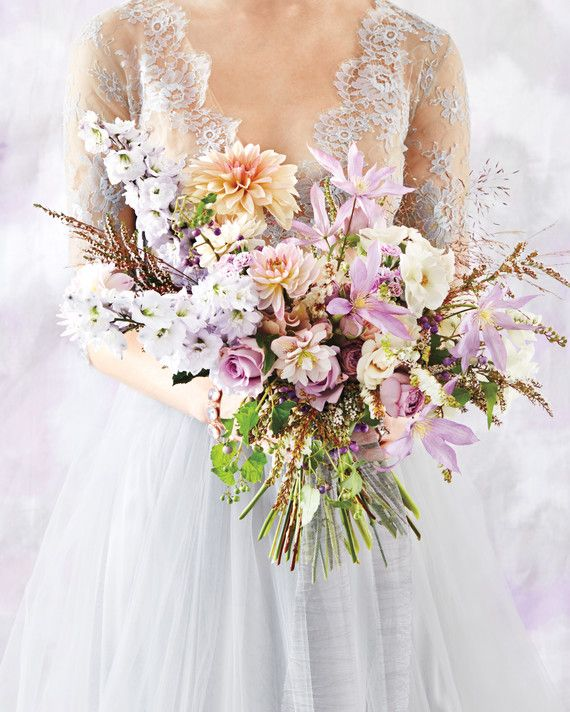 "Every wedding is romantic. But filling your day with pale grays and the lightest of lavenders is the color equivalent of saying, ""Love. Lives. Here."" And carrying a billowy bouquet of dahlias, clematis, delphiniums, hellebores, andromeda, and garden roses only adds to the otherworldly mood."