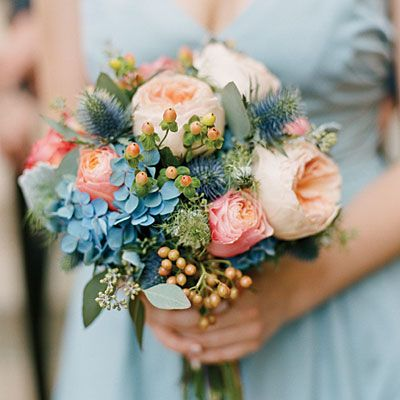 Gorgeous Blue Accents http://thefullbouquetblog.com/2012/05/25/coral-peach-and-blue-wedding-flowers/ Coral dahlias, peach juliet roses, blue hydrangea, blue thistle, peach viburnum berry, queen annes lace, and free spirit roses were used to create these lovely bouquets.