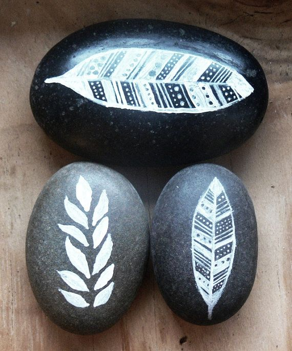 hand-painted river rocks decor - white on dark grey - leaves and feathers.