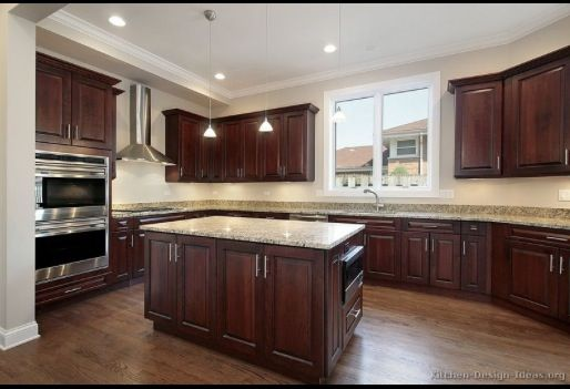 Kitchen with cherry wood cabinets, cherry wood floors and light granite counter tops