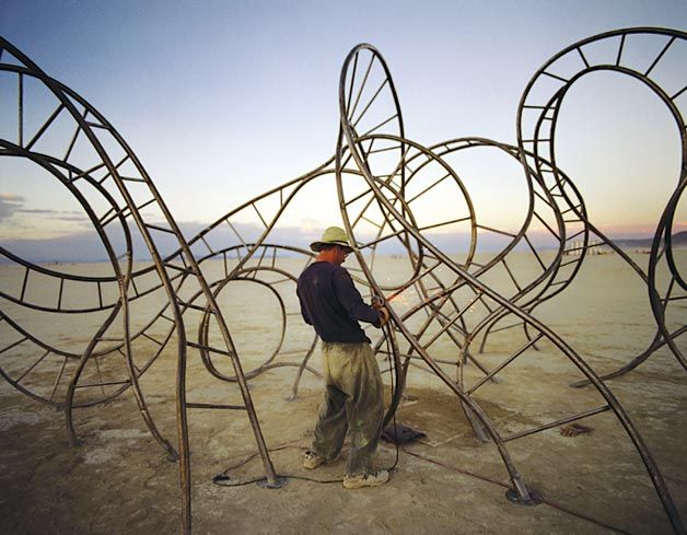 """Linka A. Odom (West Hollywood, CA)  Photographed August 2003, Black Rock Desert, NV    Odom was at the Burning Man arts festival when she came upon Michael Christian welding the final pieces of his sculpture Klimax. """"I love the lighting and the sparks from the welder's torch,"""" she says. """"It makes me smile."""""""