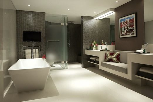 Spacious bathroom: The spacious and dark mosaic room featured a large freestanding bathtub with a television, his and he...
