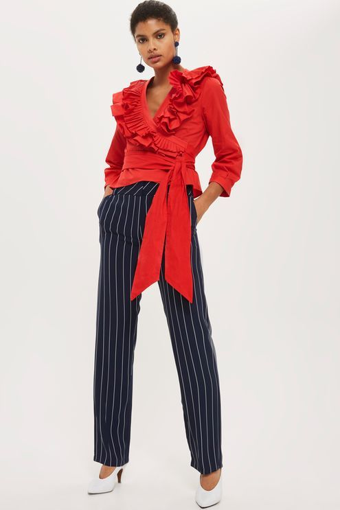 We're loving this red poplin wrap top. In an elegant pleated design with ruffle detailing and an oversized waist tie, style with a pencil skirt and court shoes for office elegance.
