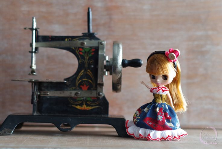 """Antique German made toy sewing machine next to a 4"""" doll. The little hand wheel still works!"""