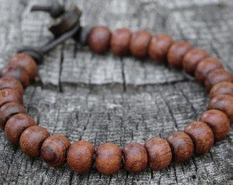 Bracelet pour homme en cuir de perles mala. Cette pièce se compose de perles en bois marrons naturel (8mm), perles en corne naturelle disque (6mm) et une perle fermoir en bois de coco, enfilées sur un cuir marron durable de haute qualité. J'utilise une perle et boucle fermoir de style qui est sécurisé et garanti pour rester fermé. Doit être robuste, indémodable et durable... comme bracelet d'un homme.  J'utilise seulement la plus haute qualité cordon en cuir disponible sur le marché. Il…