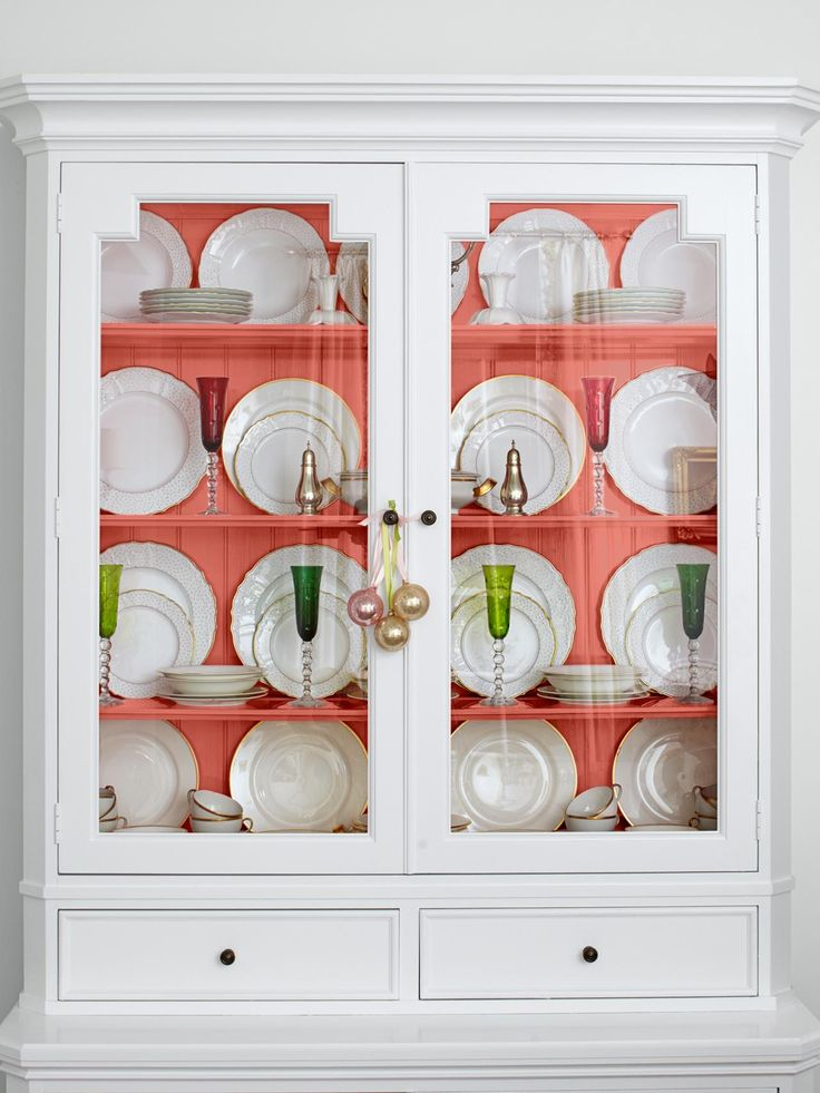 Turn a basic glass-front cabinet into a colorful accent by painting the inside back and shelves. Here, white dishes pop agaist the new soft pink hue. For a similar look, try Cool Melon by Behr. See the rest of this colorful home featured in HGTV Magazine.