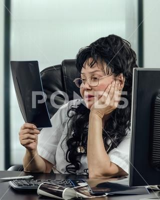 Telemedicine female doctor looks at x-ray attentively - Stock Photo | by verbaska
