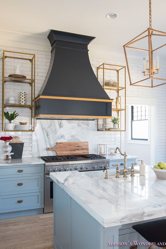 A black French kitchen hood, painted in Sherwin Williams Inkwell, is accented with gold trim and it's flanked by brass shelving. Beautiful Homes of Instagram