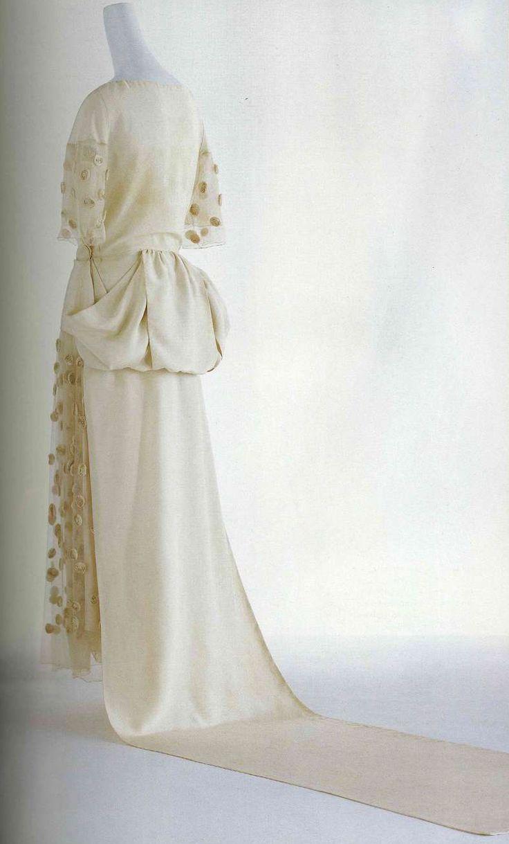 Подвенечное платье. Мадлен Вионне, около 1922. Белый шелковый фай и тюль, длина до конца лодыжки, прямое полотнище задней части юбки, переходящее в трен, украшения в виде роз из шелкового фая от Лесажа.