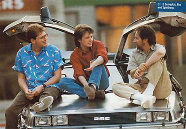 Robert Zemeckis, Michael J. Fox and Steven Spielberg having a chat on the hood of the DeLoreon from Back to the Future.