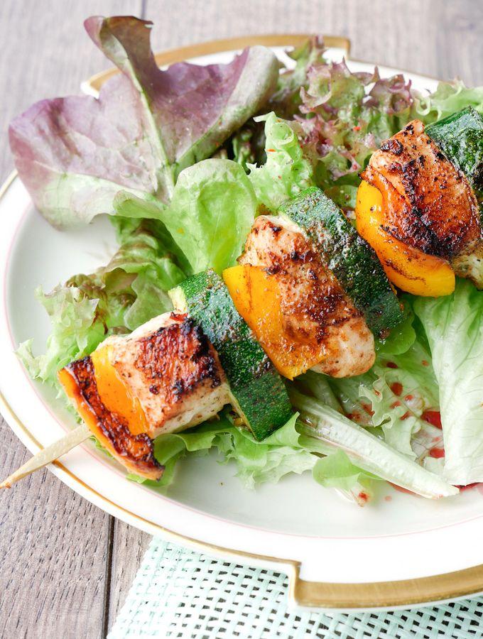 Grillspieße mit Hähnchen und Zucchini auf grünem Salat