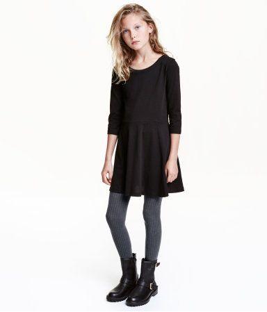 Schwarz. CONSCIOUS. Kleid aus weichem Bio-Baumwolljersey. In der Taille abgesetztes Modell mit glockigem Rock und 3/4-Ärmeln.