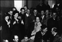 """Paris.  27th August 1944. A party given in the home of the Paris Vogue editor Michel de Brunhoff, shortly after the liberation of Paris, brought together John MORRIS (rear center with glasses). On his right: Robert CAPA. On his left (glasses): David SEYMOUR """"Chim"""". Foreground in uniform Lee MILLER. Behind her, man in tweed jacket: Henri CARTIER-BRESSON."""