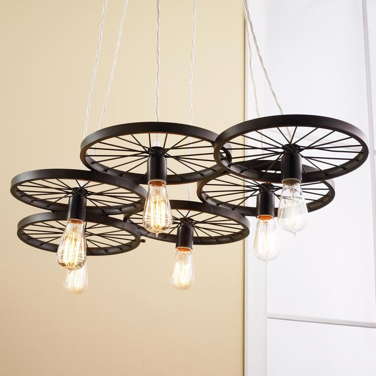 Vintage Spoke Wire Wheel ChandelierSpoke wire wheels seem to spin overhead on our exclusive canopy chandelier with vintage industrial appeal. The bronze spoke rims hold 6 medium base bulbs for great illumination over an island, workspace or long dining table. Cycling enthusiasts and antique car buffs alike will especially enjoy this fun sculptural ceiling light.