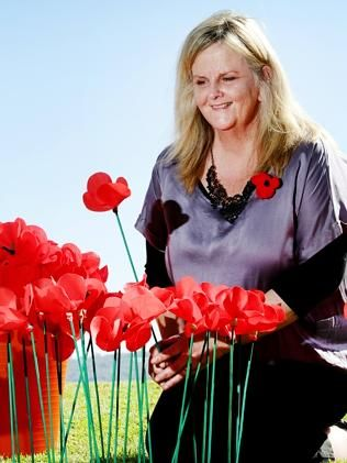 Merril Jackson prepares to place some of poppies in Gosford to mark the centenary of the