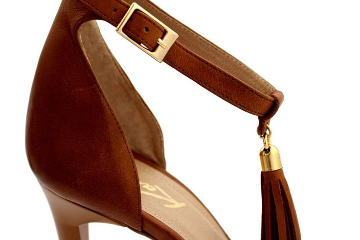 Brązowe sandałki z frędzlem - Kati  Czy Twoje idealne sandałki na szpilce byłyby kwintesencją prostoty i elegancji, ale jednak zawierały w sobie nutę nonszalancji? Jeśli tak, właśnie na nie trafiłaś. Wysoka, geometryczna bryła szpilki i prosty krój buta nawiązują do minimalistycznego stylu. Wyróżnikiem przełamującym surową prostotę jest zawieszony na pasku skórzany frędzel. Wszystkie metalowe części są w kolorze jasnego złota o błyszczącym wykończeniu. Zależnie od Twojej fantazji, buty te…