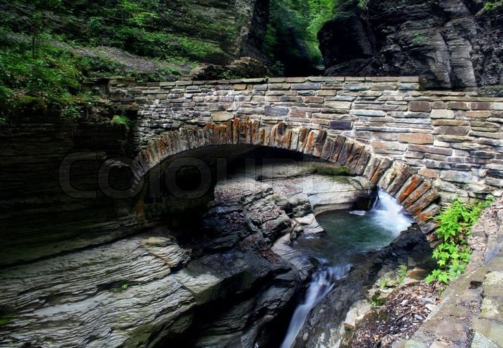 Stock image of 'Stone bridge over stream with small waterfall'