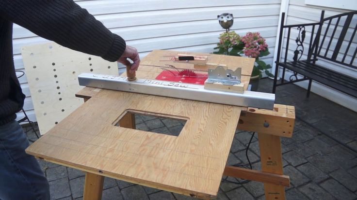 attaching the mini table saw and clamping table to the sawhorse with 3 legs