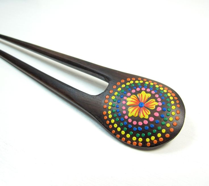 Cet accessoire de cheveux est un pique à cheveux en bois à double branches. Il est peint à la main. les piques à cheveux de Mosaik sont tous fabriqués par des artisans indiens.
