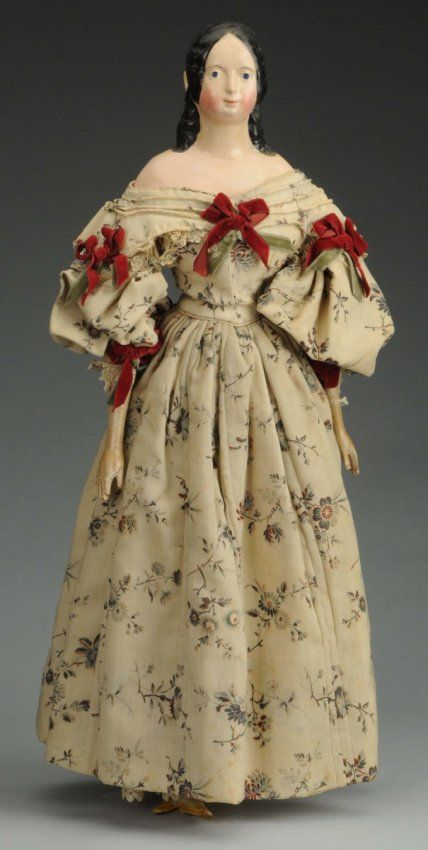 """Shoulder head with black molded hair with center part looped to behind ears with long curls down back and exposed ears, held by a molded barrette painted blue with yellow and red dots (several craze lines on shoulder); original kid body (mended at waist, crotch and knees) with wood lower arms and legs; beautifully redressed in antique fabrics and ready to display! Beautiful large example! Condition (Very Good). Size 20 - 1/2"""" T. Est $1200-1800."""