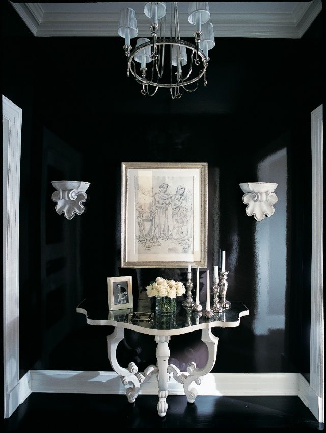 Glossy black entry walls with white trim and dark wood floors