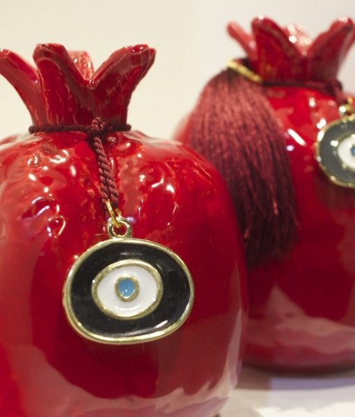 Enamelled red pomegranate with a tassel and an eye trinket.