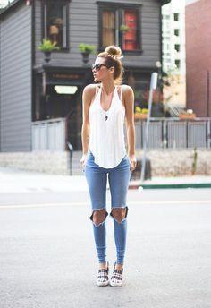 Regata branca, calça jeans rasgada no joelho, tênis sem cadarso