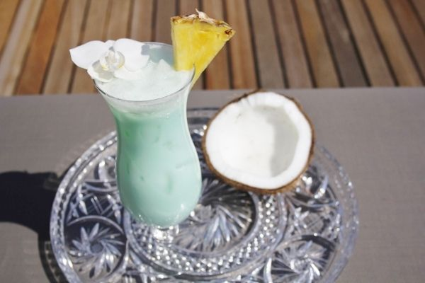 Blue Hawaiian: Blue curacao (1 part) Rum of kokos rum (1 part) Coconut milk (1,5 part) Fresh pineapple juice (1 slice & garnish) Crushed ice