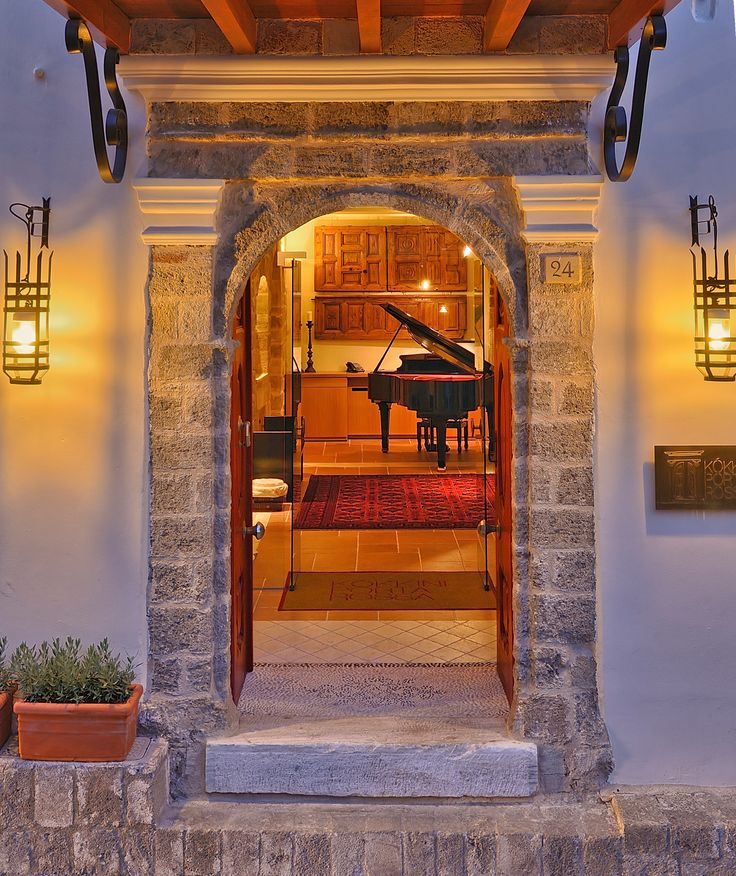 EXCLUSIVE SUITES BOUTIQUE HOTEL. MEDIEVAL TOWN, RHODES, GREECE. -  The entrance at sunset, with the red door wide open. The 340 kg marble door step was part of the staircase of a 19 century mansion in Athens.  - kokkiniporta.com
