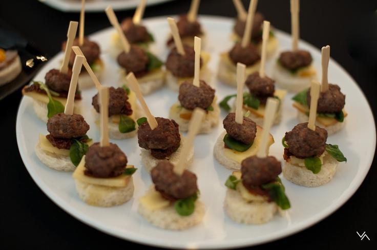 Mini burgeri din carne de vită, aromați cu chimion arăbesc și trei feluri de piper, asortați cu brânză afumată și roșii uscate la soare și marinate-n ulei de măsline, decorați cu valeriană.