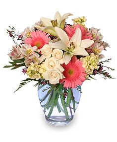 Gentle pink blooms in a clear vase. Light colors mixed together to provide just the right amount of pink.