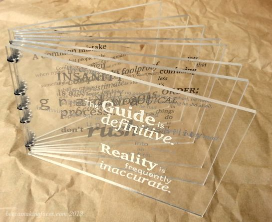 Hitchhiker's Guide to the Galaxy quote book by Becca Hirsbrunner |  There is one quote per each of the eight pages, arranged so that when the book is closed the words form a 'word cloud'. The pages are laser-cut and etched acrylic plastic and are sewn with waxed linen thread.