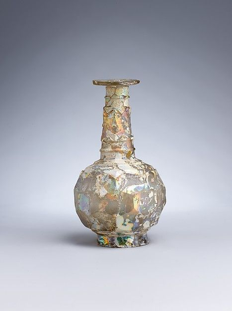 Islamic glass bottle, 9th–10th century A.D. Iran. Glass, colorless with yellowish tinge, blown, cut, 16.5 cm high. Metropolitan museum of art