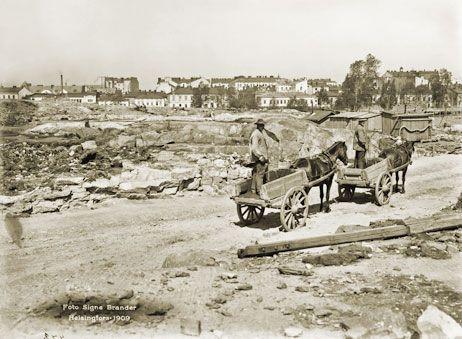 Hevoskärryjen takana tässä Eira näkymässä on Laivurinkatu. Kuva on pohjoisen päin kuvattu panoraaman osa. Hkm 1909 Signe Brander.