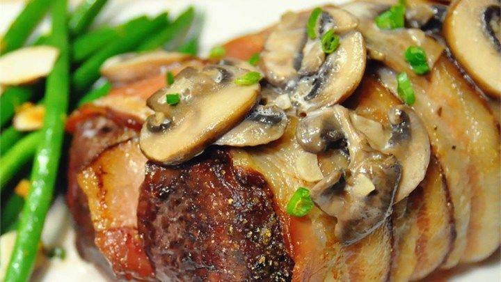 Venison tenderloins trimmed into roasts are wrapped in bacon slices, roasted, and served with a creamy mushroom sauce in this elegant recipe.
