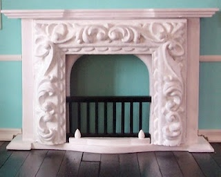"""Found a cheap wooden fireplace and cut a frame in half to glue on the front of it. Painted it all white with acrylic"" - see blog posting for original pieces"