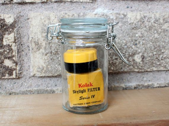 "This vintage memory lane miniature jar displays an original Kodak Skylight Filter Series IV  These miniature glass jars preserve little pieces of photography history. They are great display pieces that fit on a desk, a fire place mantel, a display shelf.  They make nice little gifts for any photo enthusiast or just to show a little piece of history. Start collecting them all.  The jars are 3# tall and 1 ½""diameter."