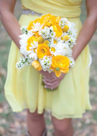 A charming and simple idea for a bridesmaid bouquet with yellow and white flowers. Notice there is no symmetry to the bouquet. Also, a beautiful contrast of strong true yellow and white colors against a more pastel bridesmaid dress.